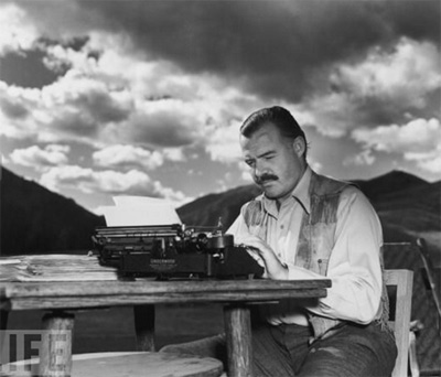 Ernest Hemingway typing at his desk outdoors.